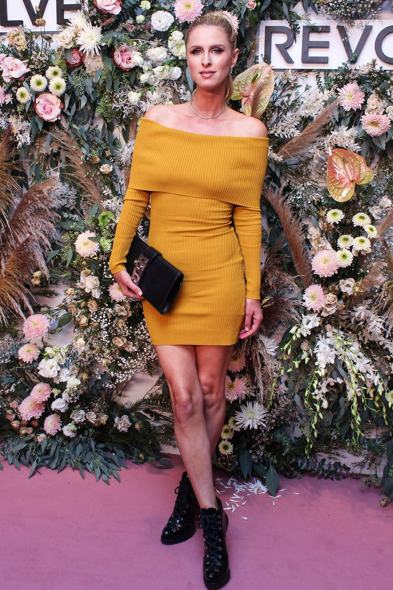 Nicky Hilton shows off her slender physique in a mustard yellow ribbed knit mini dress