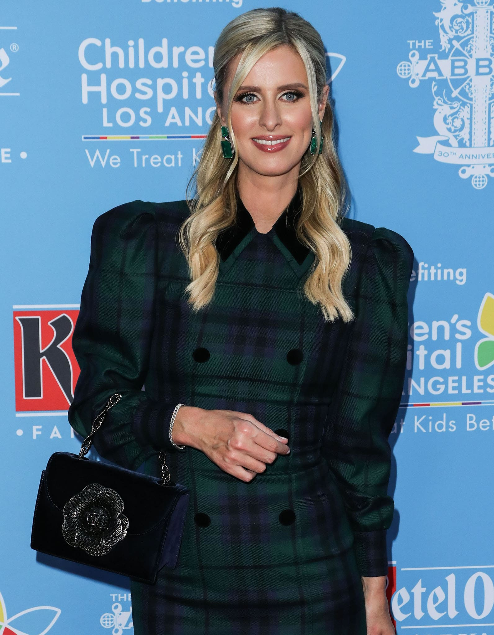 Nicky Hilton partially ties her wavy tresses to the back and wears subtle smokey eyeshadow and pink lip gloss