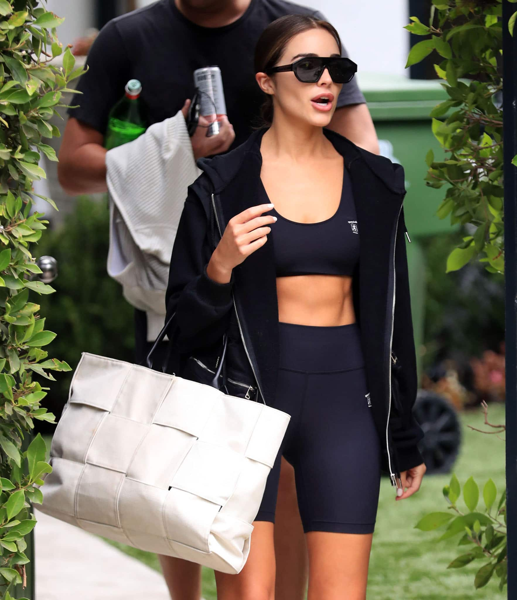 Olivia Culpo carries a Bottega Veneta Arca tote and hides eyes behind Karen Walker sunnies
