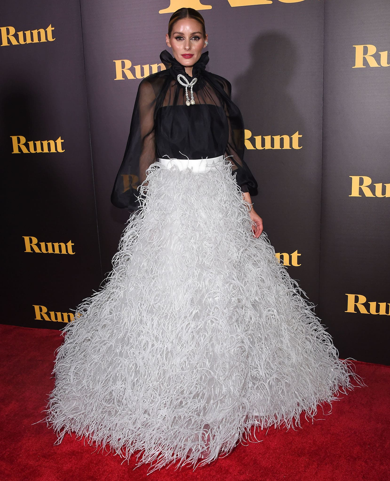 Olivia Palermo steals the spotlight in a two-piece Monique Lhuillier Spring 2022 look featuring a black sheer blouse and a white feathered ball gown skirt