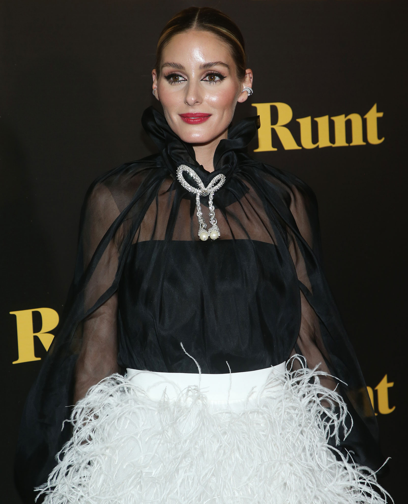 Olivia Palermo wears a center-parted braided ponytail with cat eyeliner and red lipstick