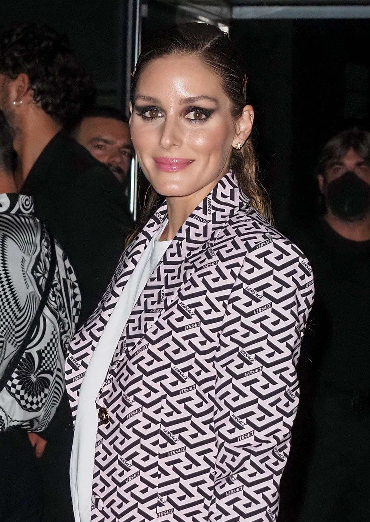 Olivia Palermo wears a slicked-back ponytail with smokey cat-eye makeup and pink lipstick