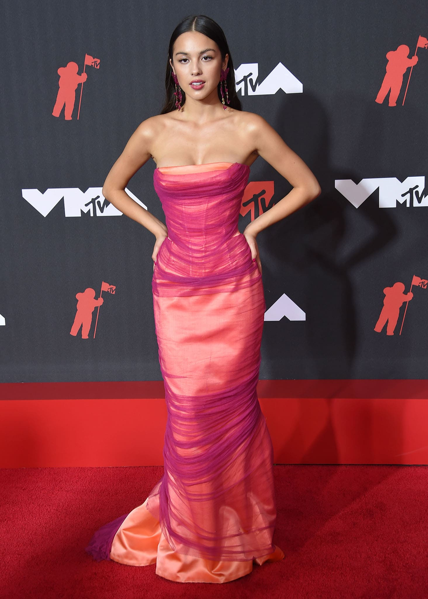 Olivia Rodrigo showcases her slim figure in a peach Atelier Versace gown with purple tulle overlay