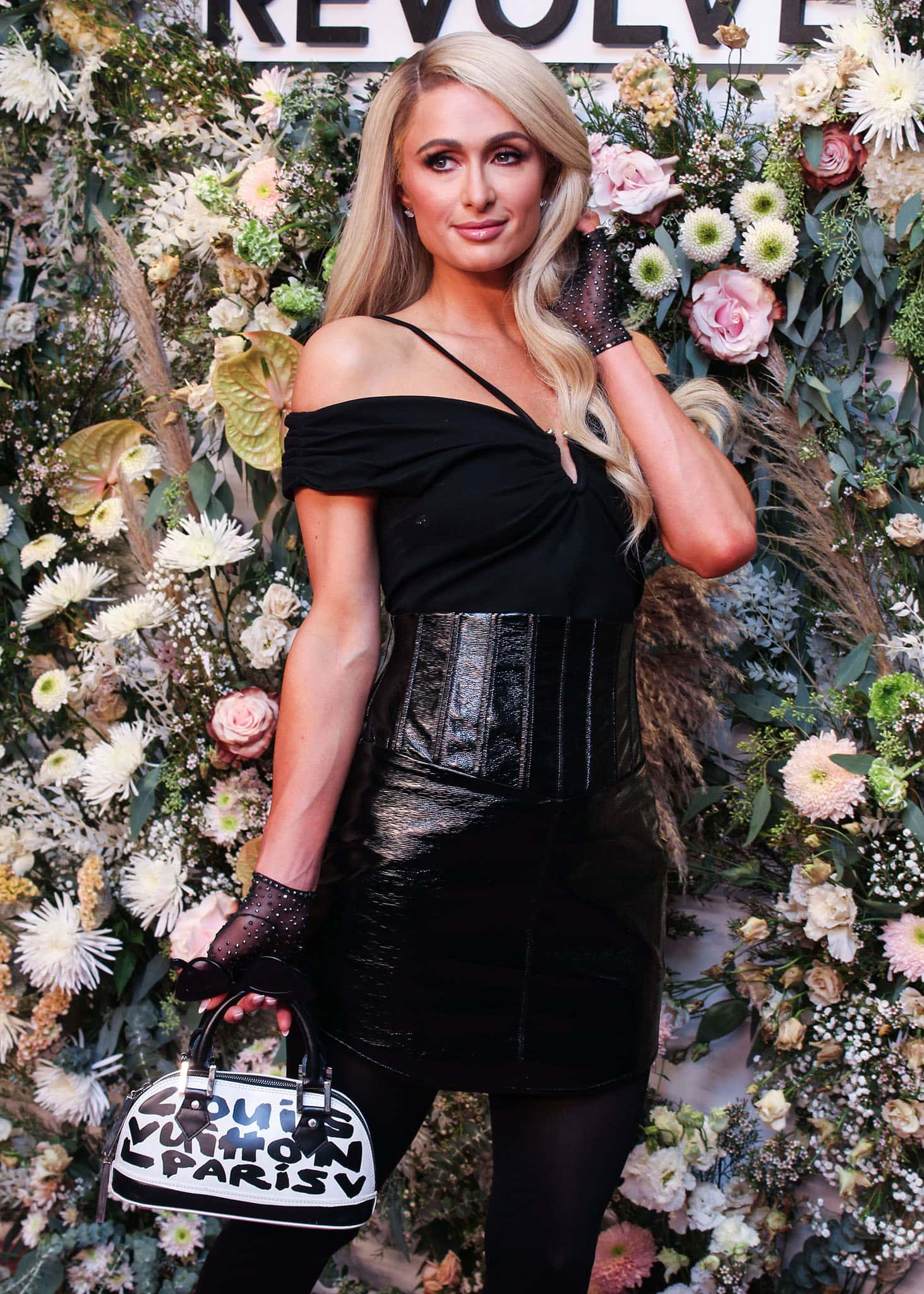 Paris Hilton wears wavy hair extensions with pink lipstick and black sheer fingerless gloves