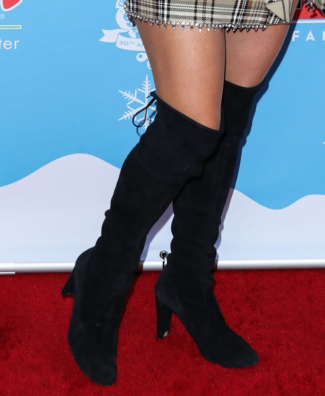Paris Hilton completes her holiday look with Stuart Weitzman Highland over-the-knee boots