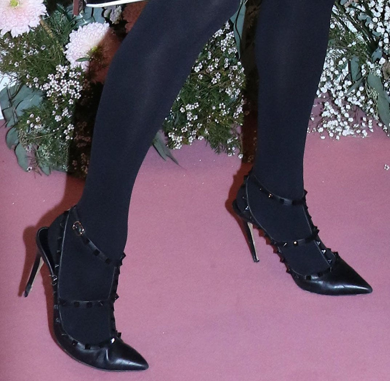 Paris Hilton completes an all-black look with black tights and Valentino Garavani Rockstud pumps