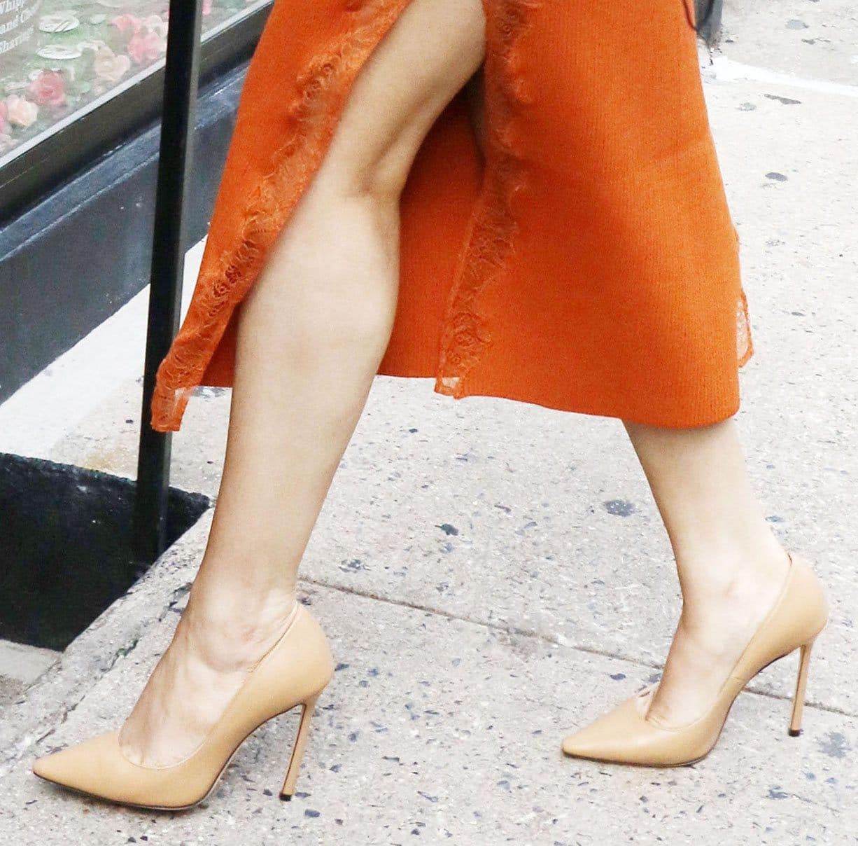 Selena Gomez teams her orange dress with Jimmy Choo Romy nude pumps