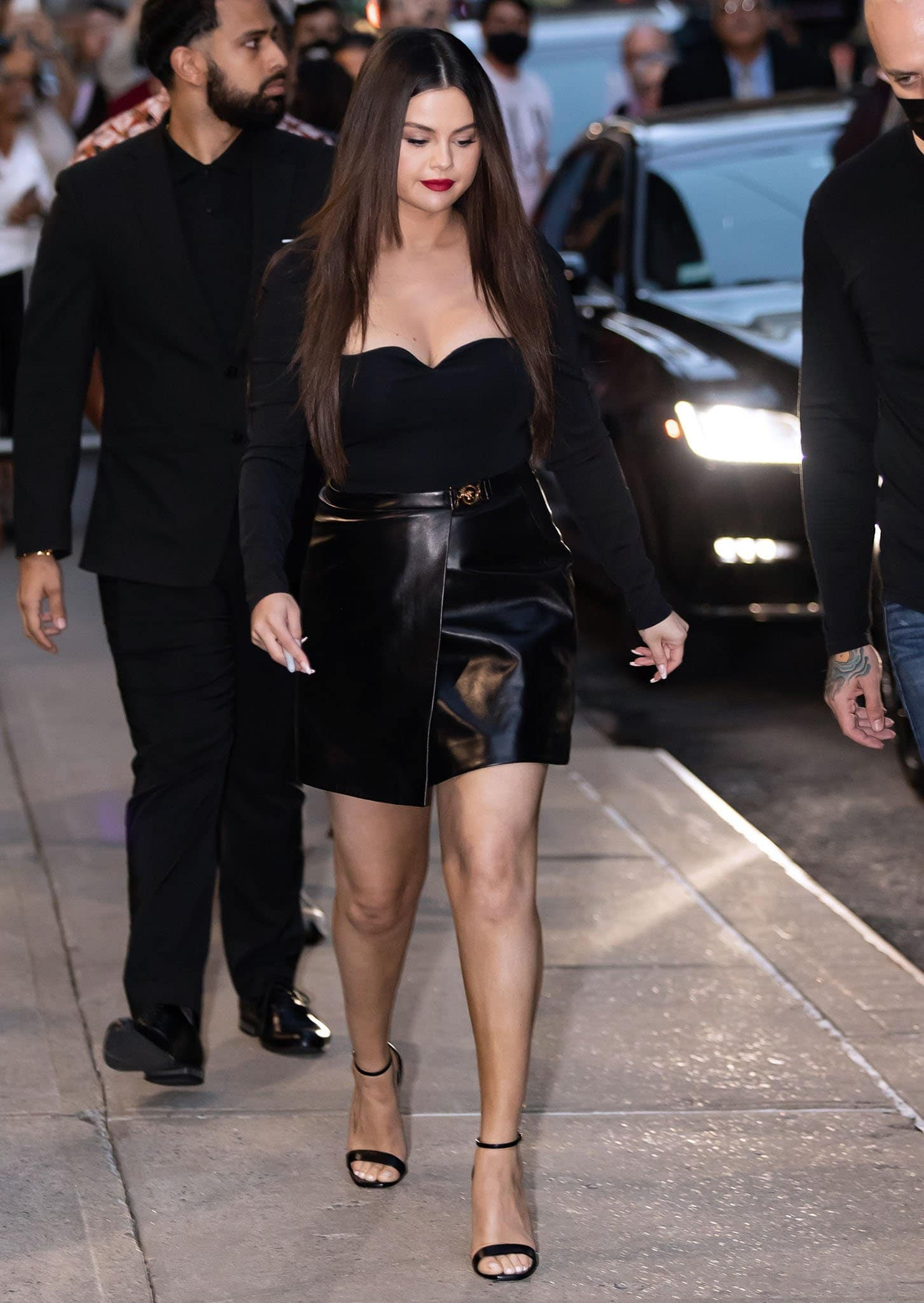 Selena Gomez parades her legs in Versace leather mini skirt and cleavage-baring jersey bodysuit