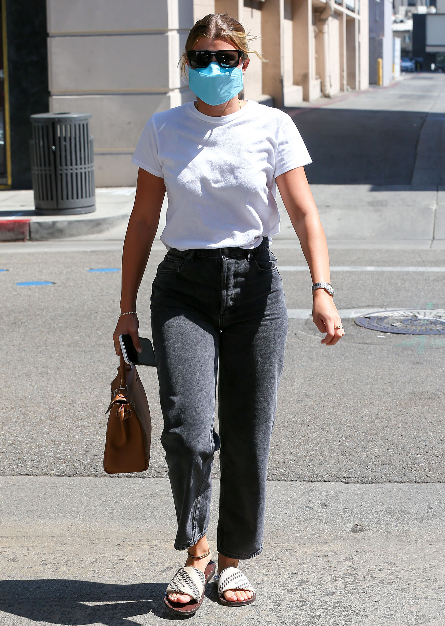 Sofia Richie wears a basic white tee with black wash high-rise mom jeans