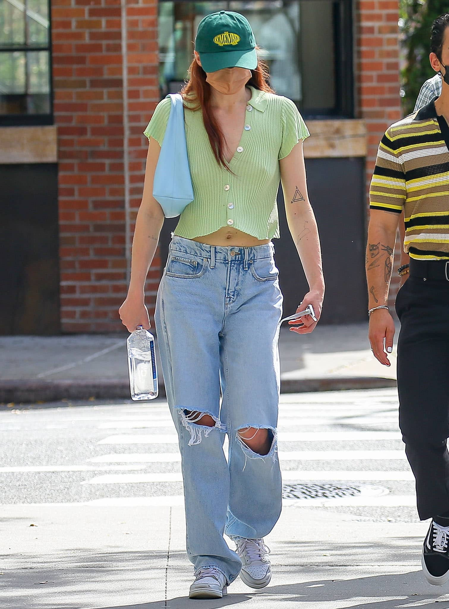 Sophie Turner flashes her abs in Calle Del Mar rib-knit crop top and low-rise baggy ripped jeans