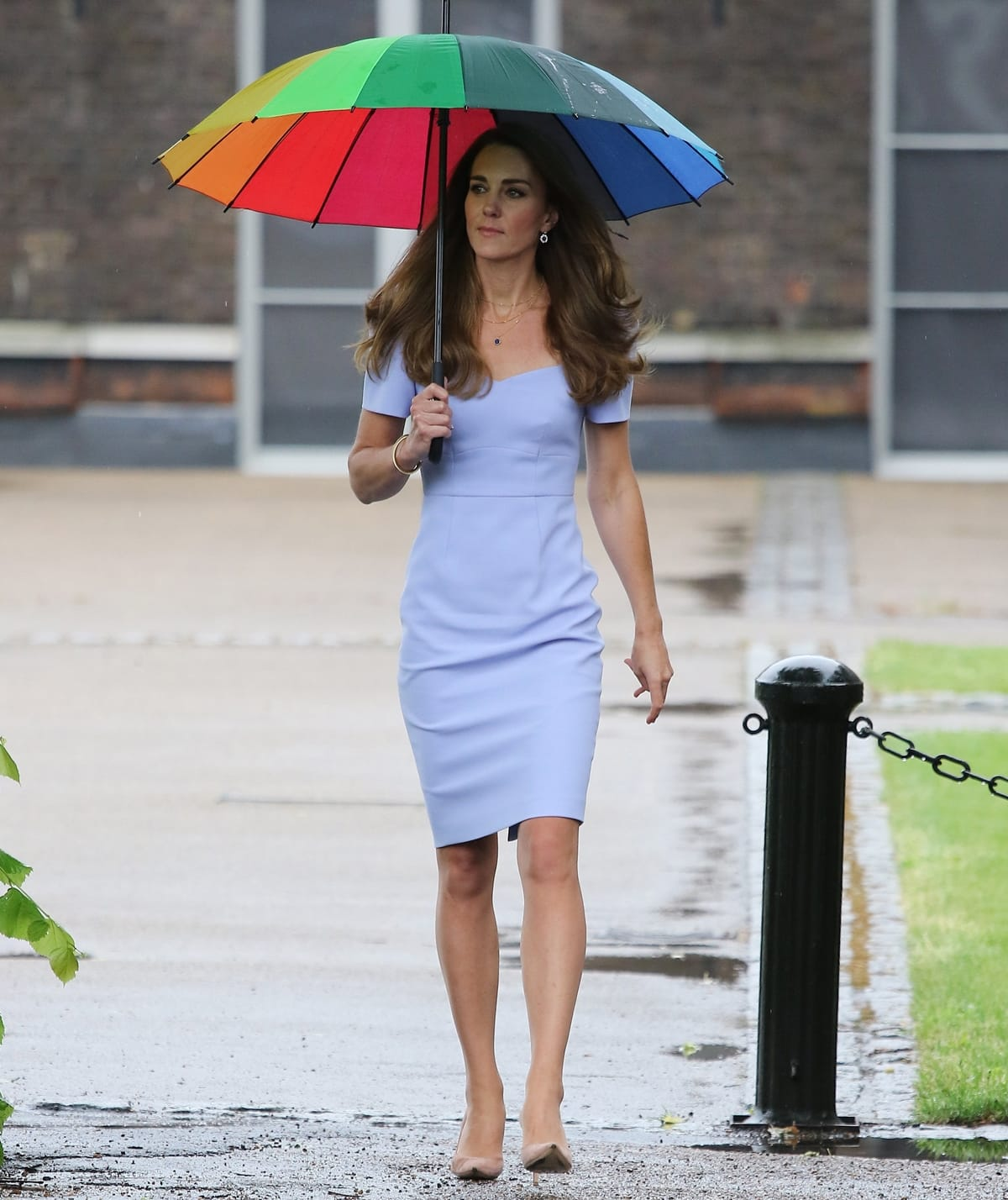 The Duchess of Cambridge in a pale blue shift dress from the Royal Ascot x L.K.B collection shelters from the rain under an umbrella as she arrives at Kensington Palace