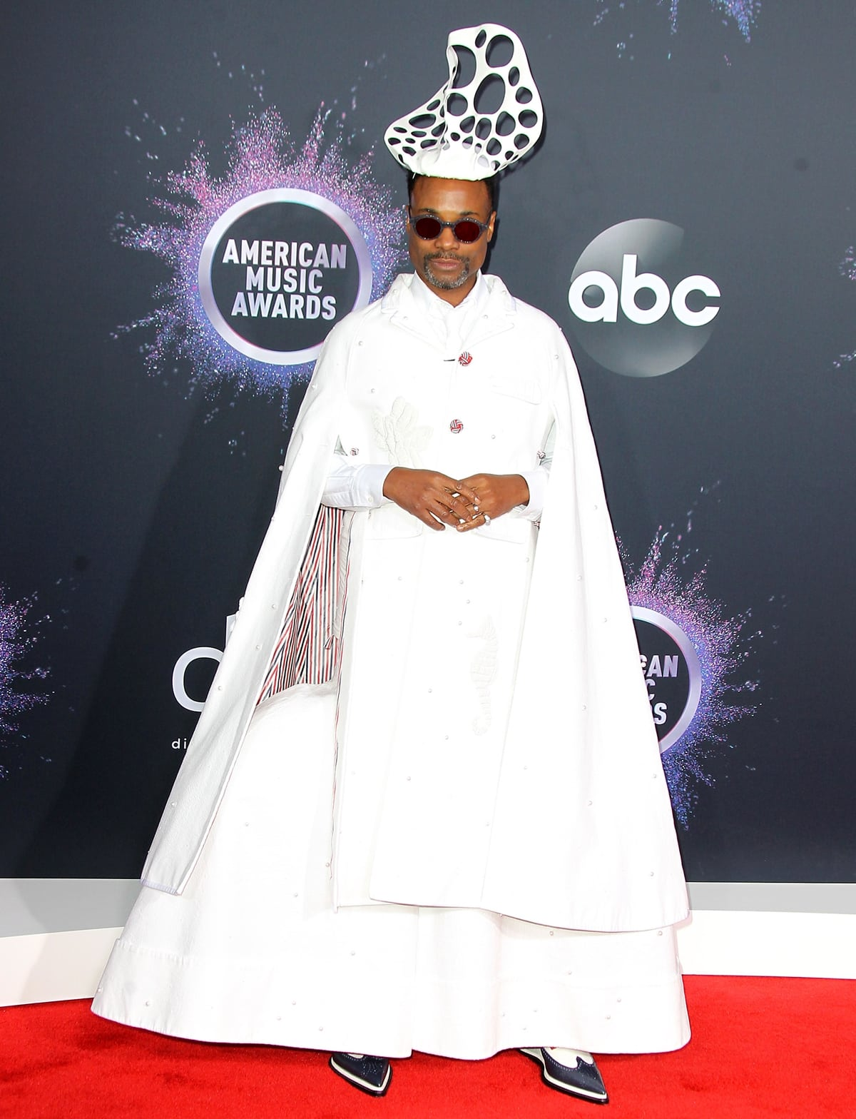 Billy Porter in a white outfit from Thom Browne's Spring 2020 collection a and cutout headpiece from Stephen Jones Millinery at the 47th American Music Awards