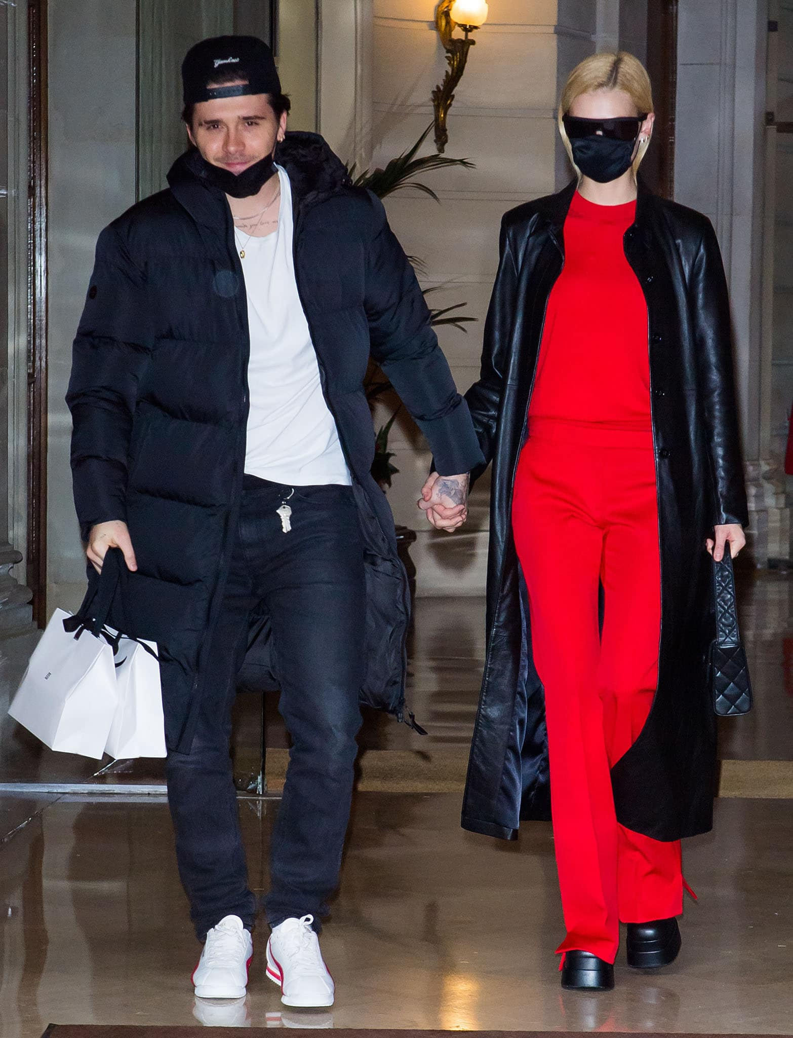 Nicola Peltz styles her red outfit with a black leather coat, sunglasses, face mask, and chunky boots