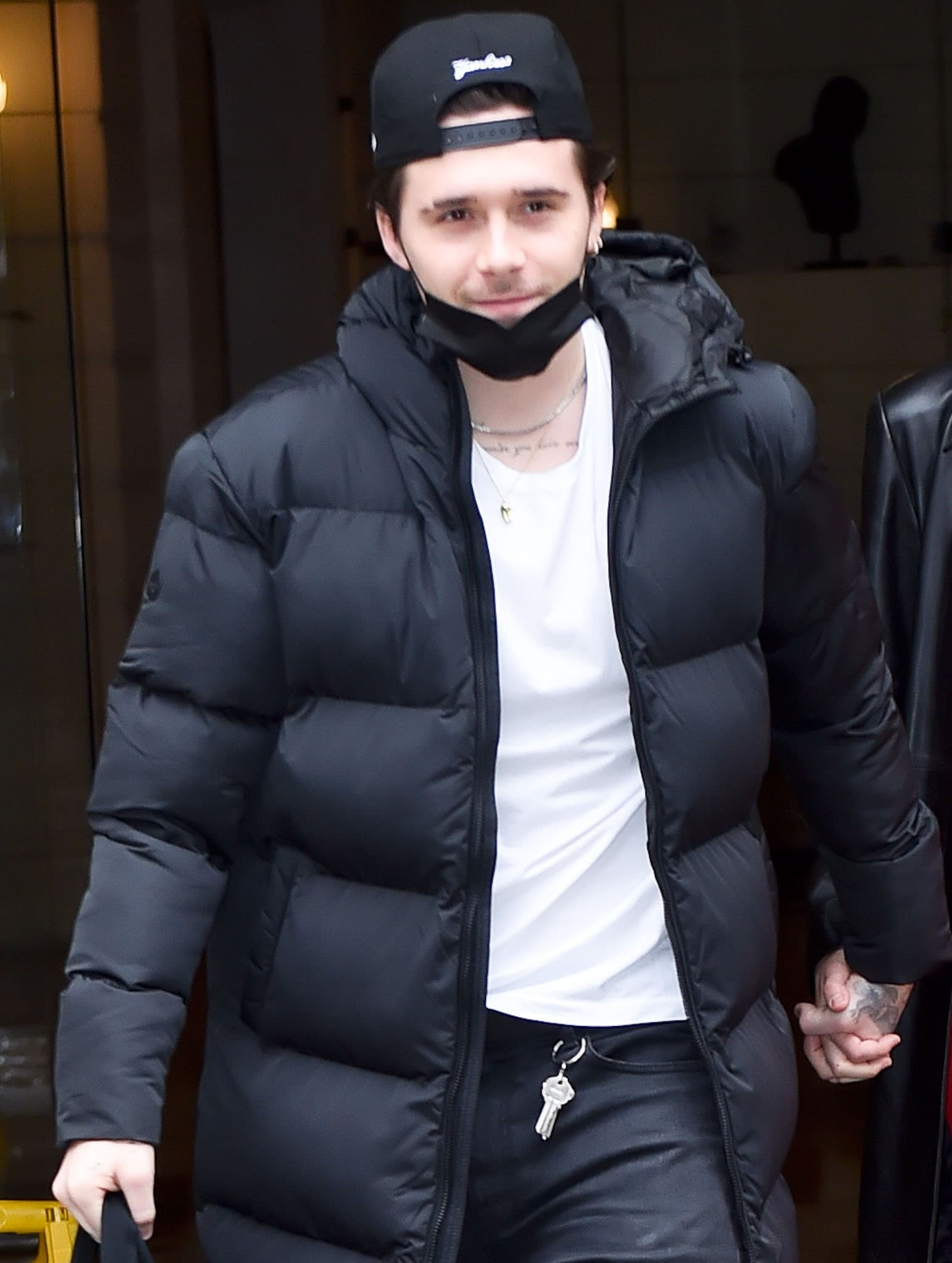 Brooklyn Beckham looks cool in a black Superdry puffy duvet coat with a white tee underneath