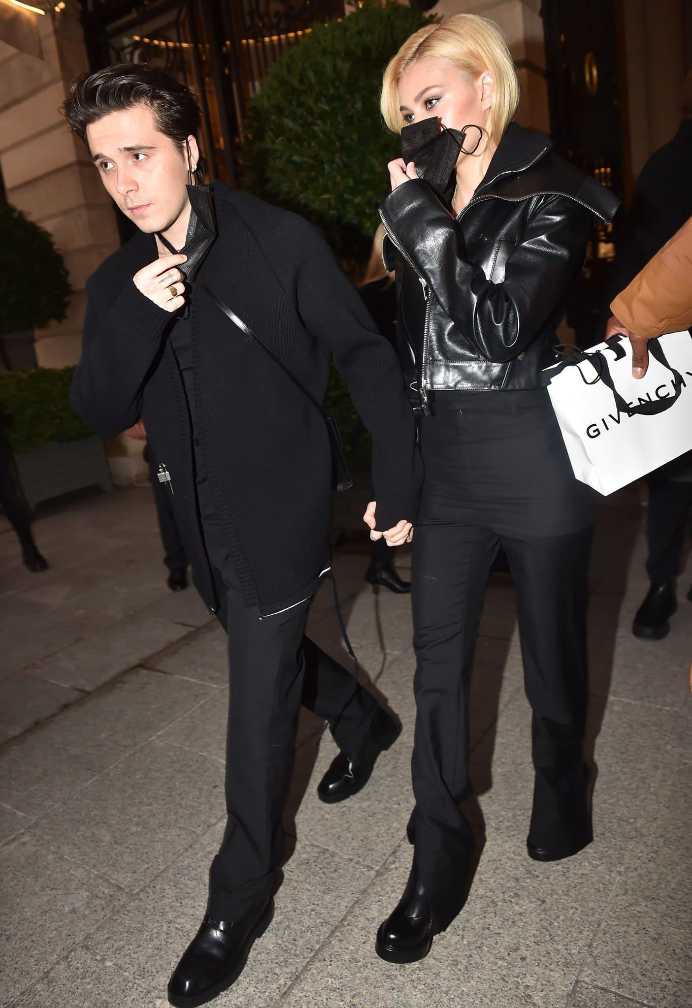 Brooklyn Beckham and Nicola Peltz wear coordinating black looks, with Nicola in a black leather biker jacket and Brooklyn in a rib-knit cardigan