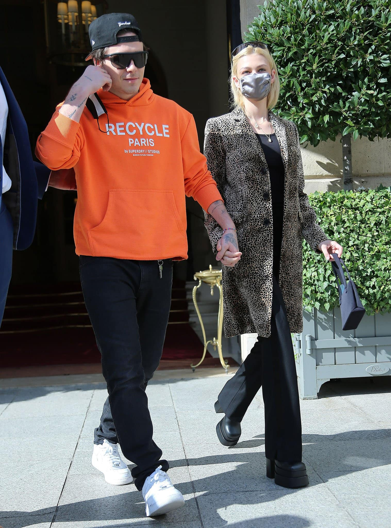 Brooklyn Beckham wears a bold orange Superdry hoodie with black jeans and Nike Air Force 1 shoes