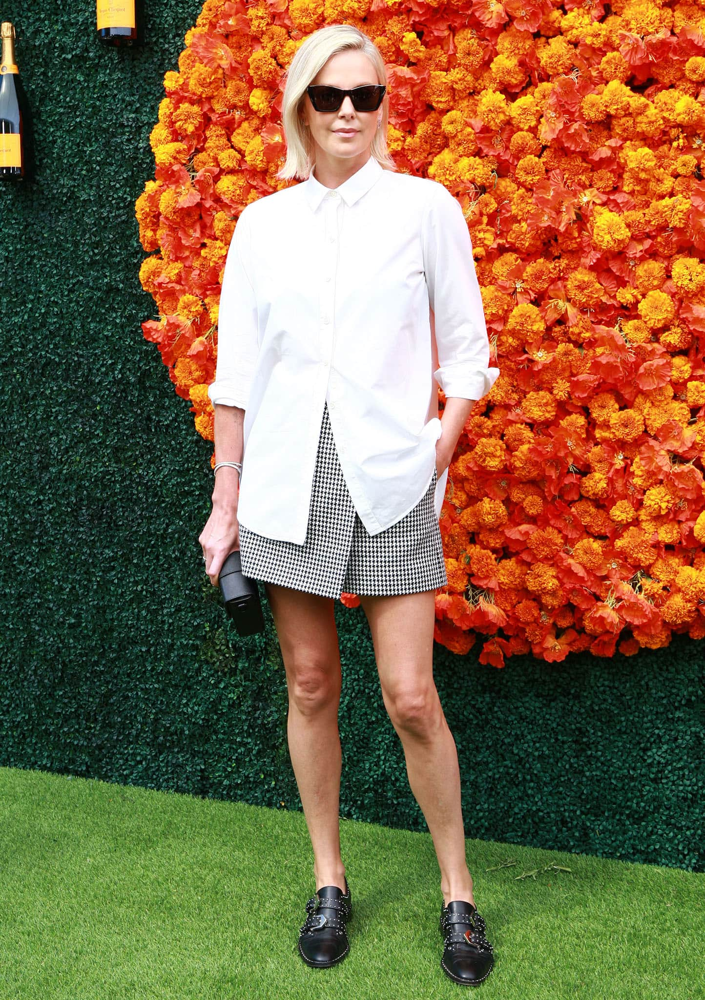 Charlize Theron flaunts her legs in a houndstooth mini skirt with a basic white shirt