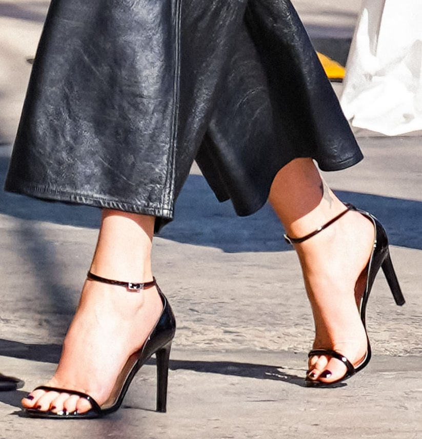 Charlize Theron shows off her black pedicure in black patent leather heels
