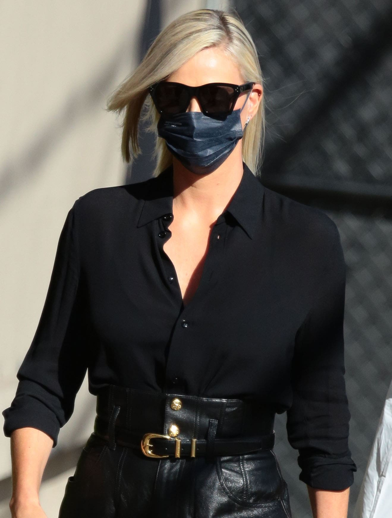 Charlize Theron hides her face behind oversized sunglasses and a black face mask