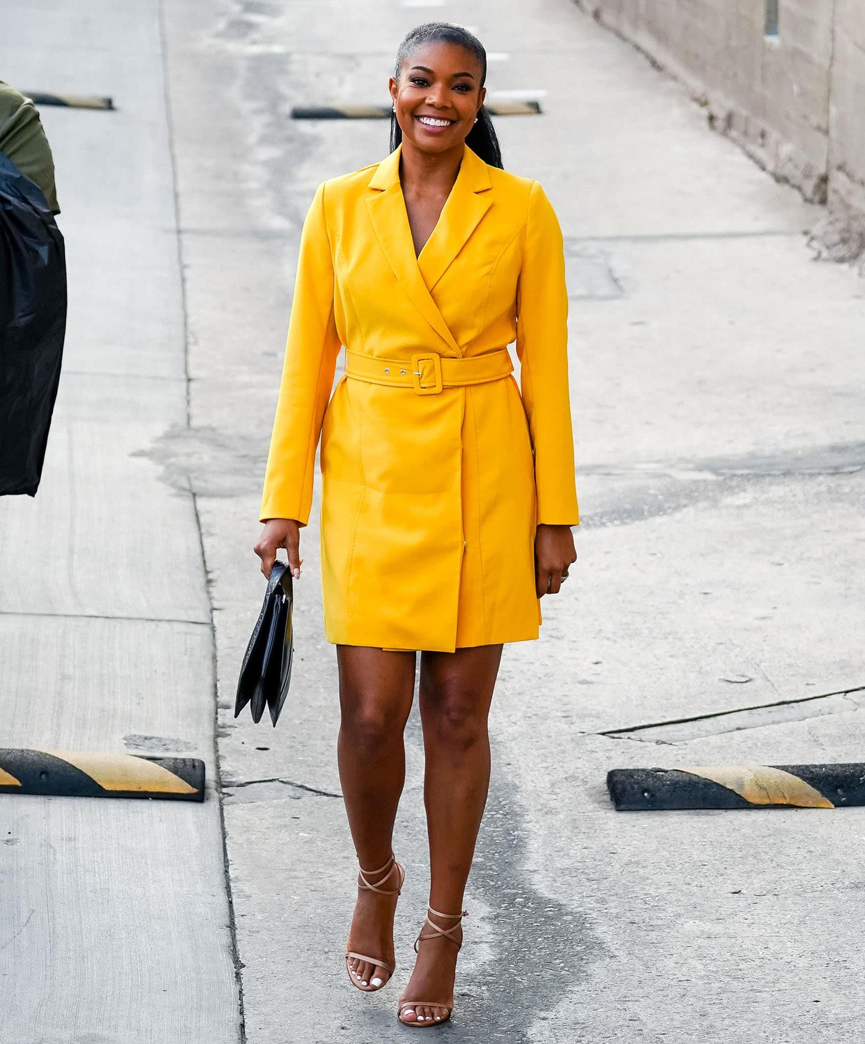 Gabrielle Union swaps her fringe dress for a yellow coat dress outside Jimmy Kimmel Live studio on September 28, 2021
