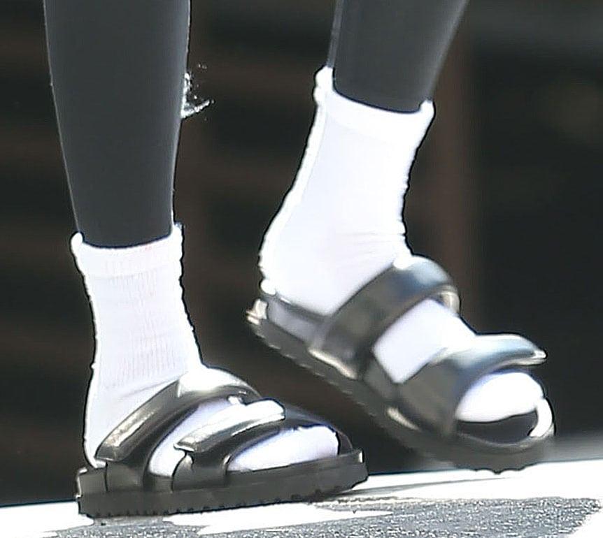 Hailey Bieber slips her feet into a pair of white tube socks and Gia Borghini's Perni double-strap sandals