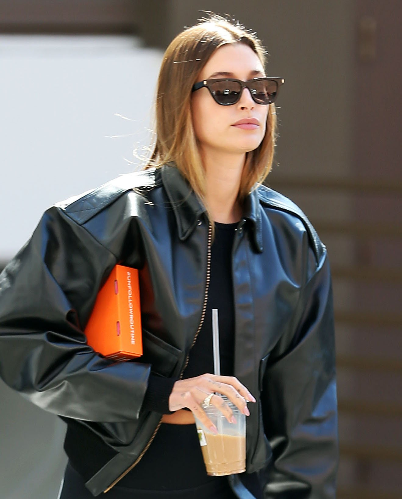 Hailey Bieber wears glossy tresses down and styles her casual athleisure with black sunglasses