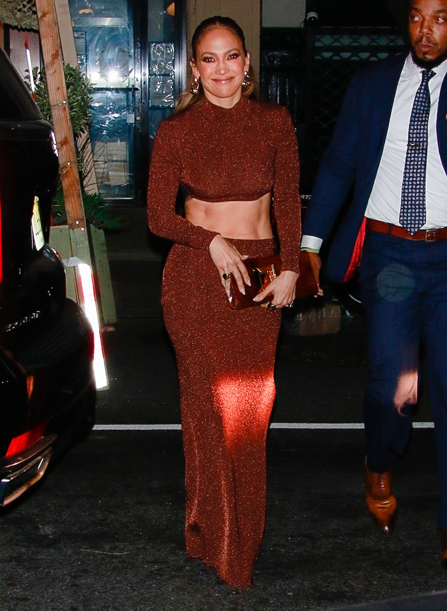 Jennifer Lopez flashes a smile as she shows off her abs in a two-piece Herve Leger Resort 2022 shimmering crop top and skirt