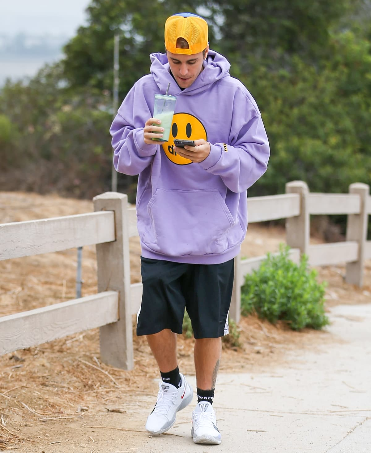 Justin Bieber wears a lavender Drew House mascot hoodie and a trucker hat while hiking in Los Angeles