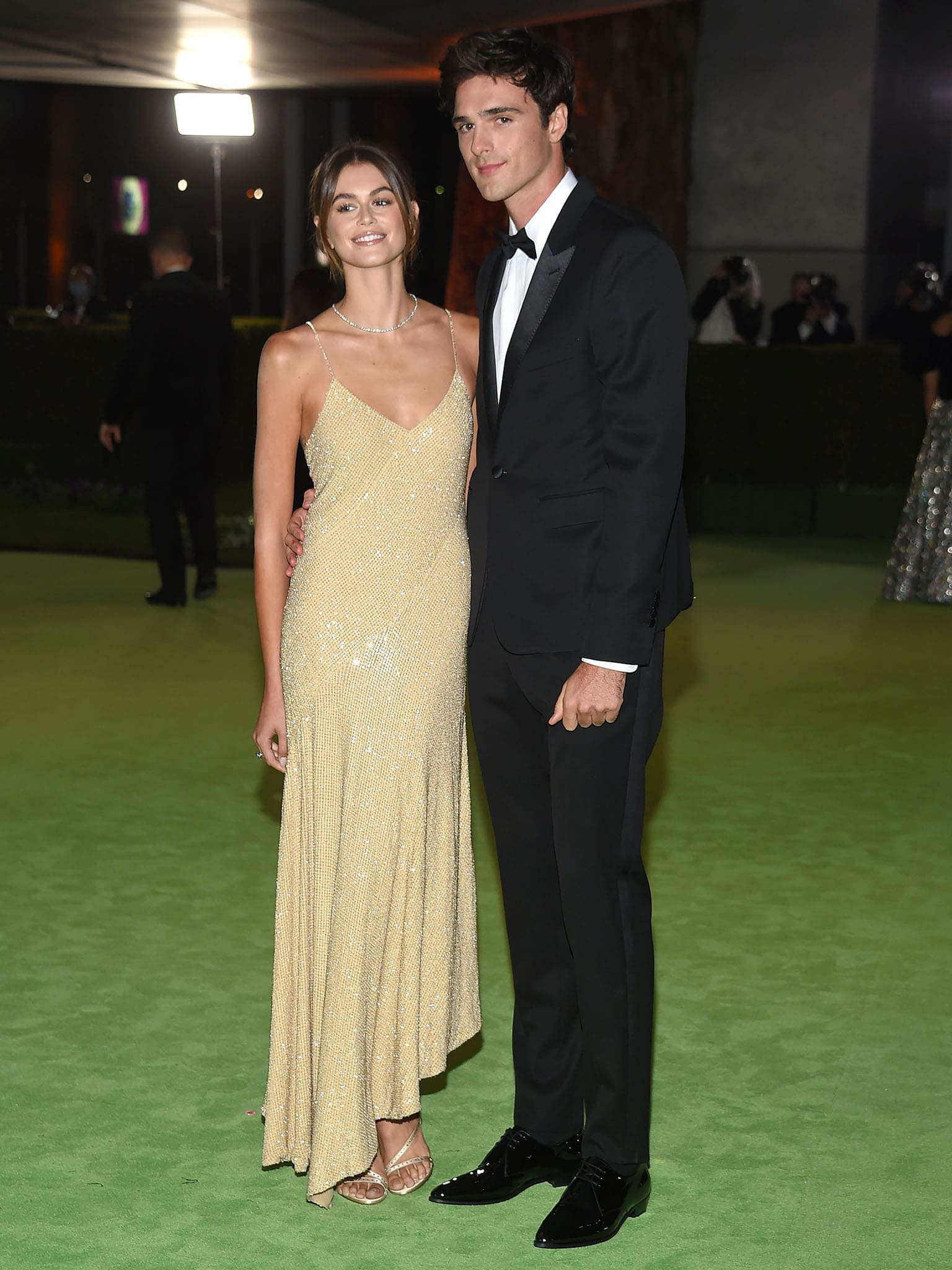 Kaia Gerber showcases her supermodel height in a slinky champagne asymmetric gown
