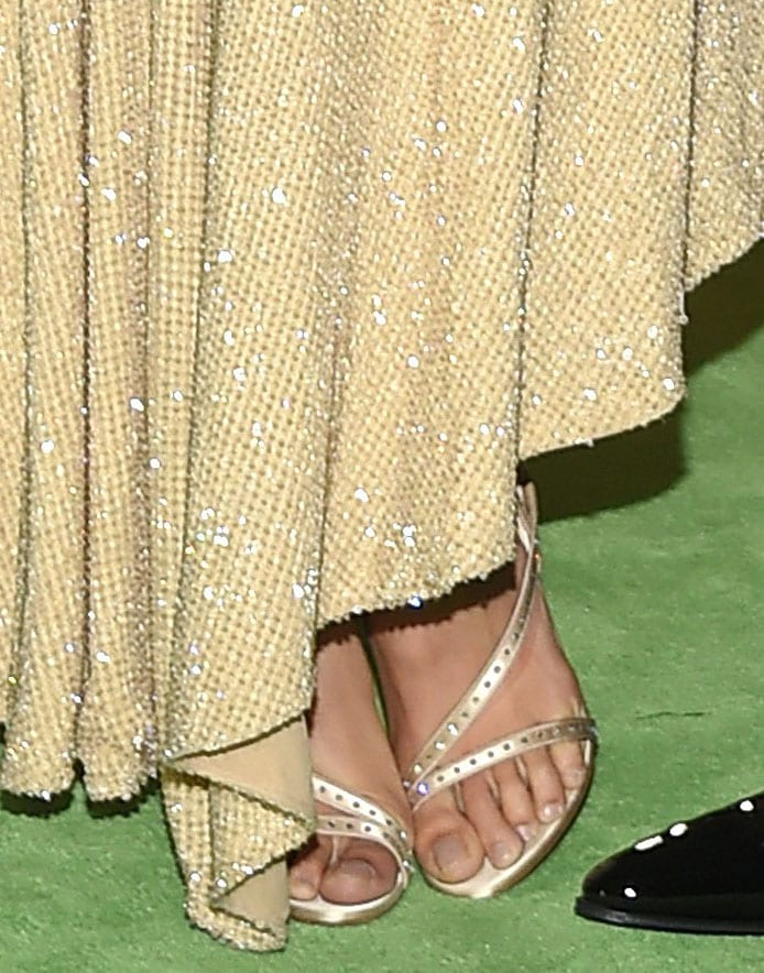 Kaia Gerber shows off her feet in open-toe metallic gold studded sandals