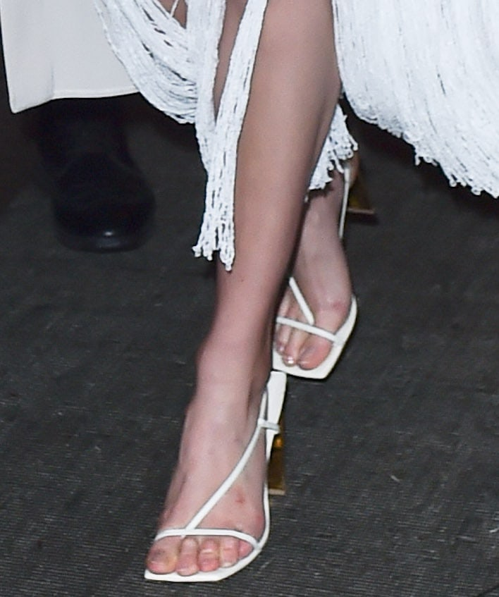 Karlie Kloss shows off her feet in white Arielle Baron Narcissus sandals with gold mirror heels