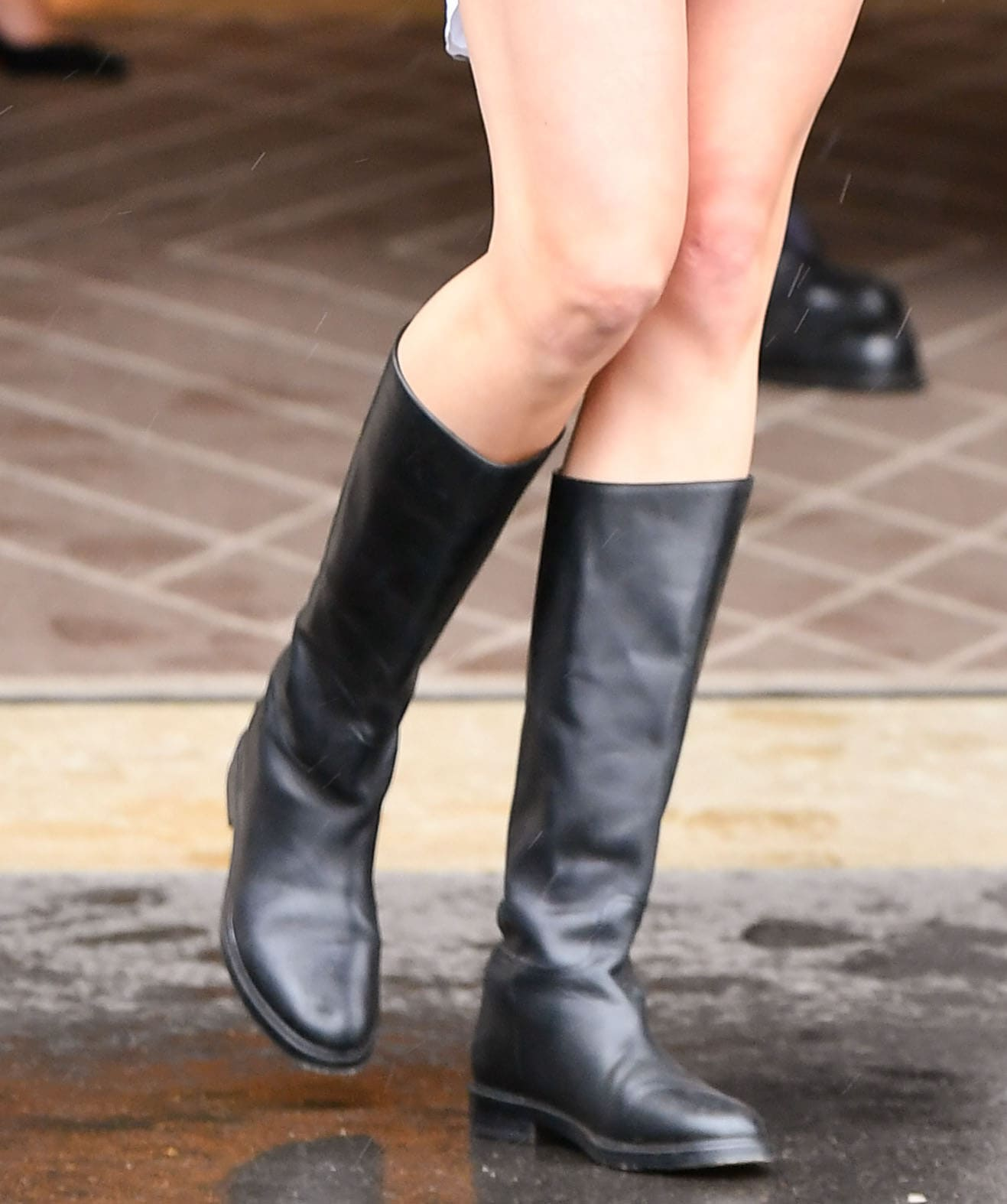 Karlie Kloss pairs her mini dress with black leather mid-calf boots