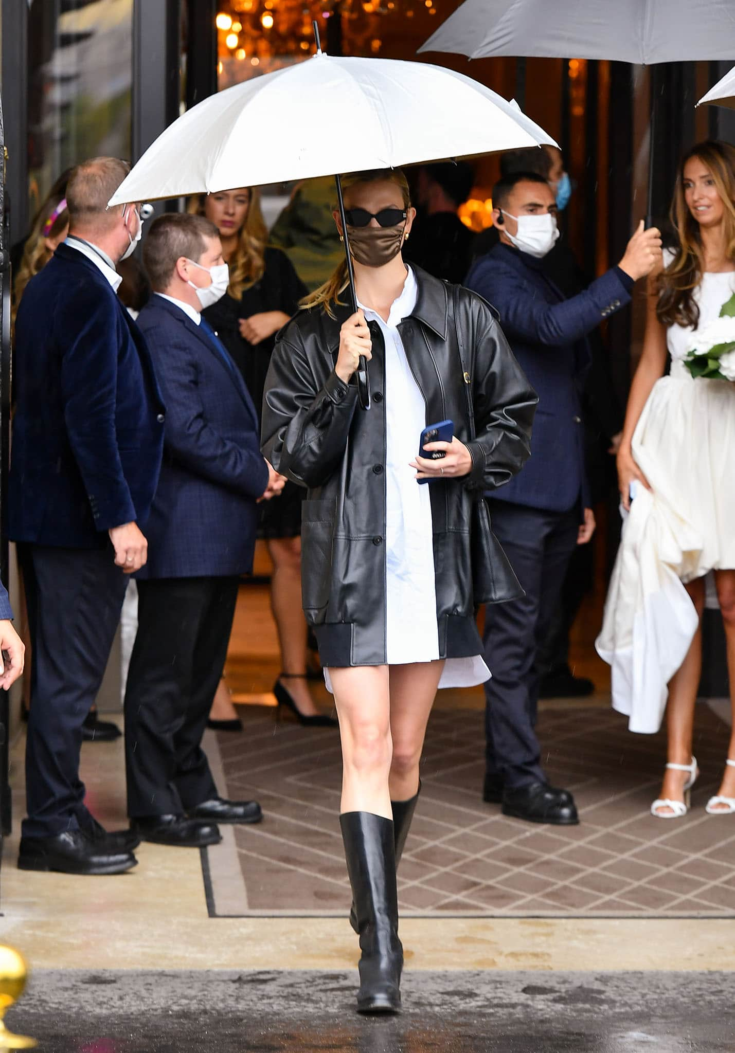 Karlie Kloss parades her legs in a Parisian chic white mini dress and black leather jacket