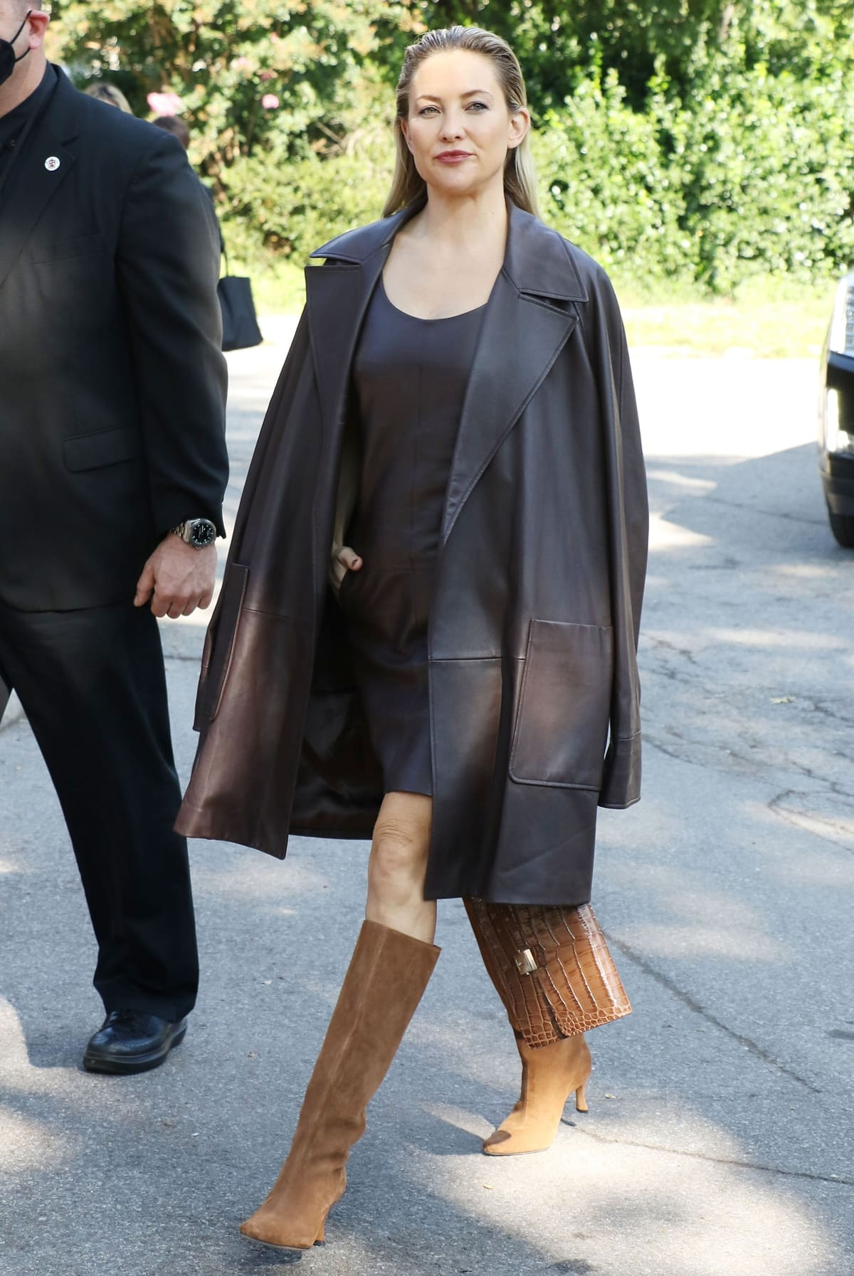 Kate Hudson in a plongé leather trench coat and a shift dress with pointy knee-high boots arrives at the Michael Kors show