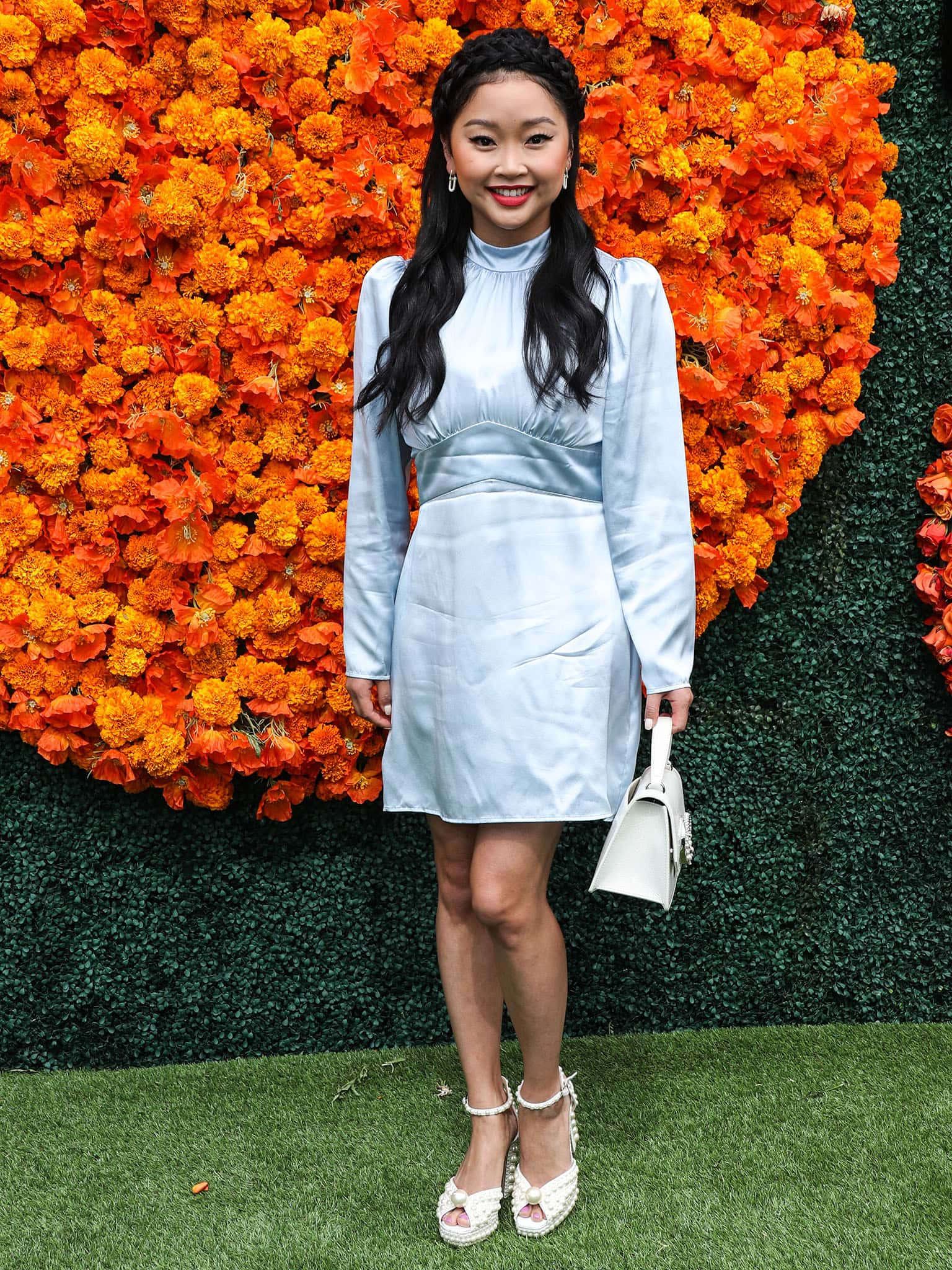 Lana Condor wears a Reformation light blue satin mini dress with puff long sleeves