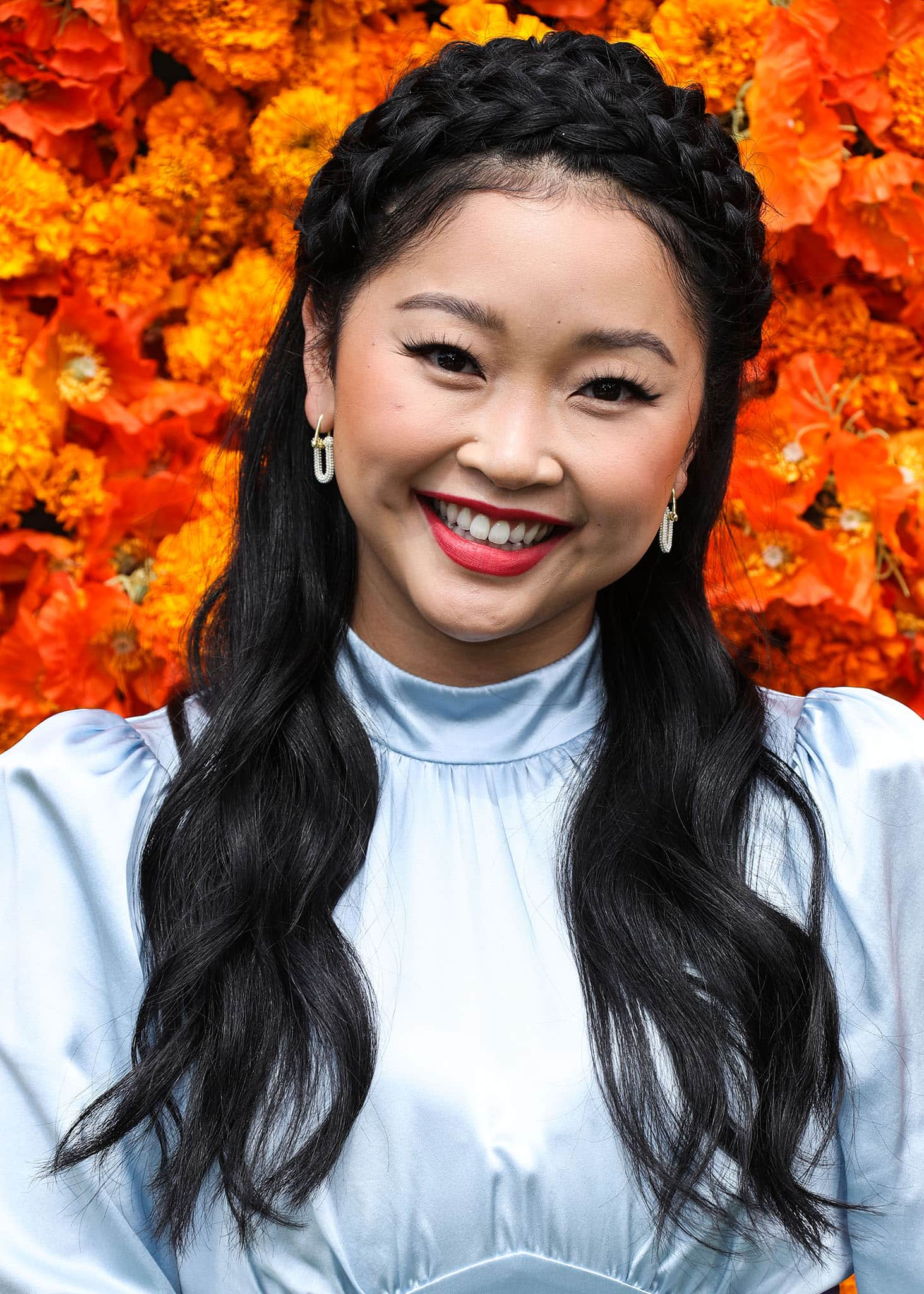 Lana Condor wears red lipstick and styles her hair in soft waves with a crown braid