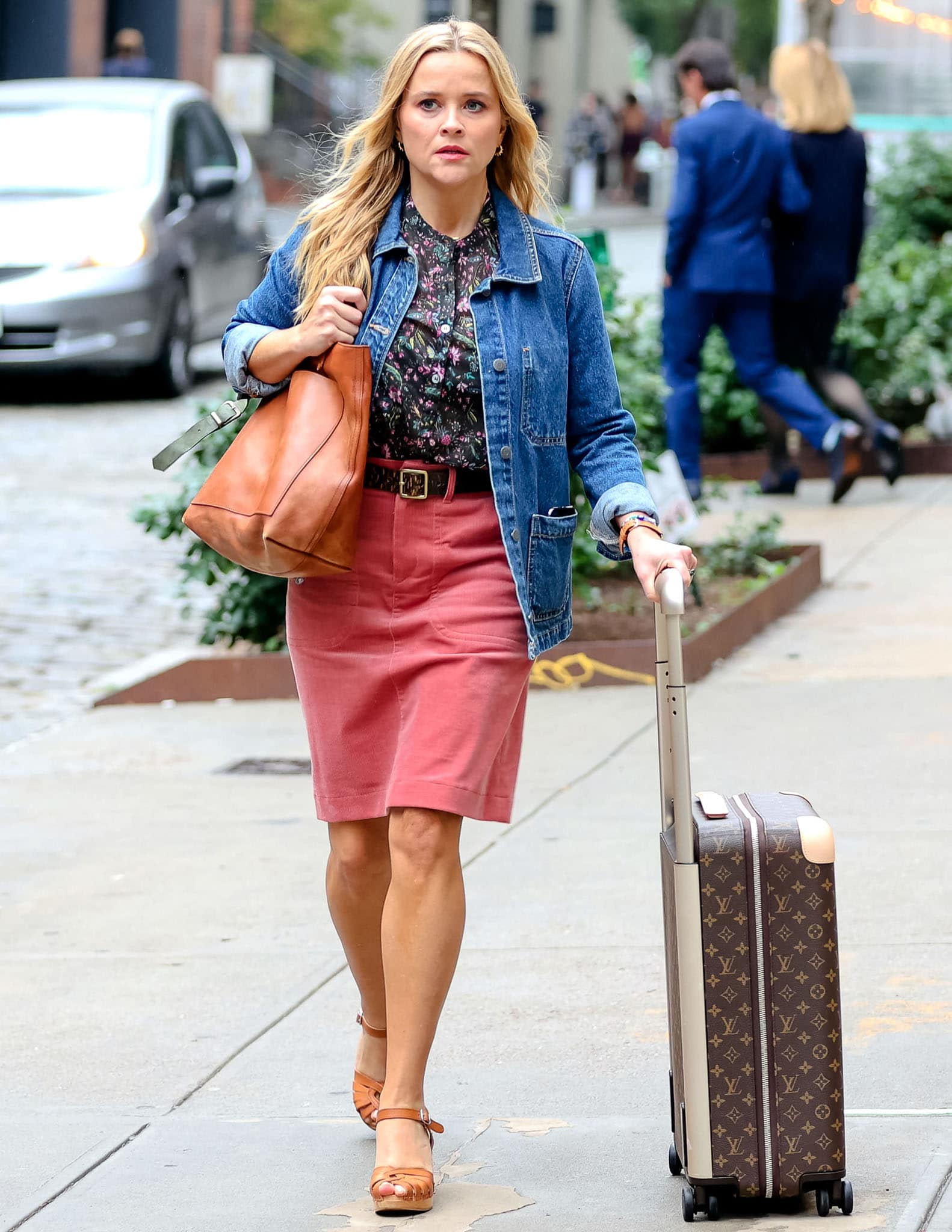 Reese Witherspoon wears a similar look with a floral shirt, pink mini skirt, and a denim jacket