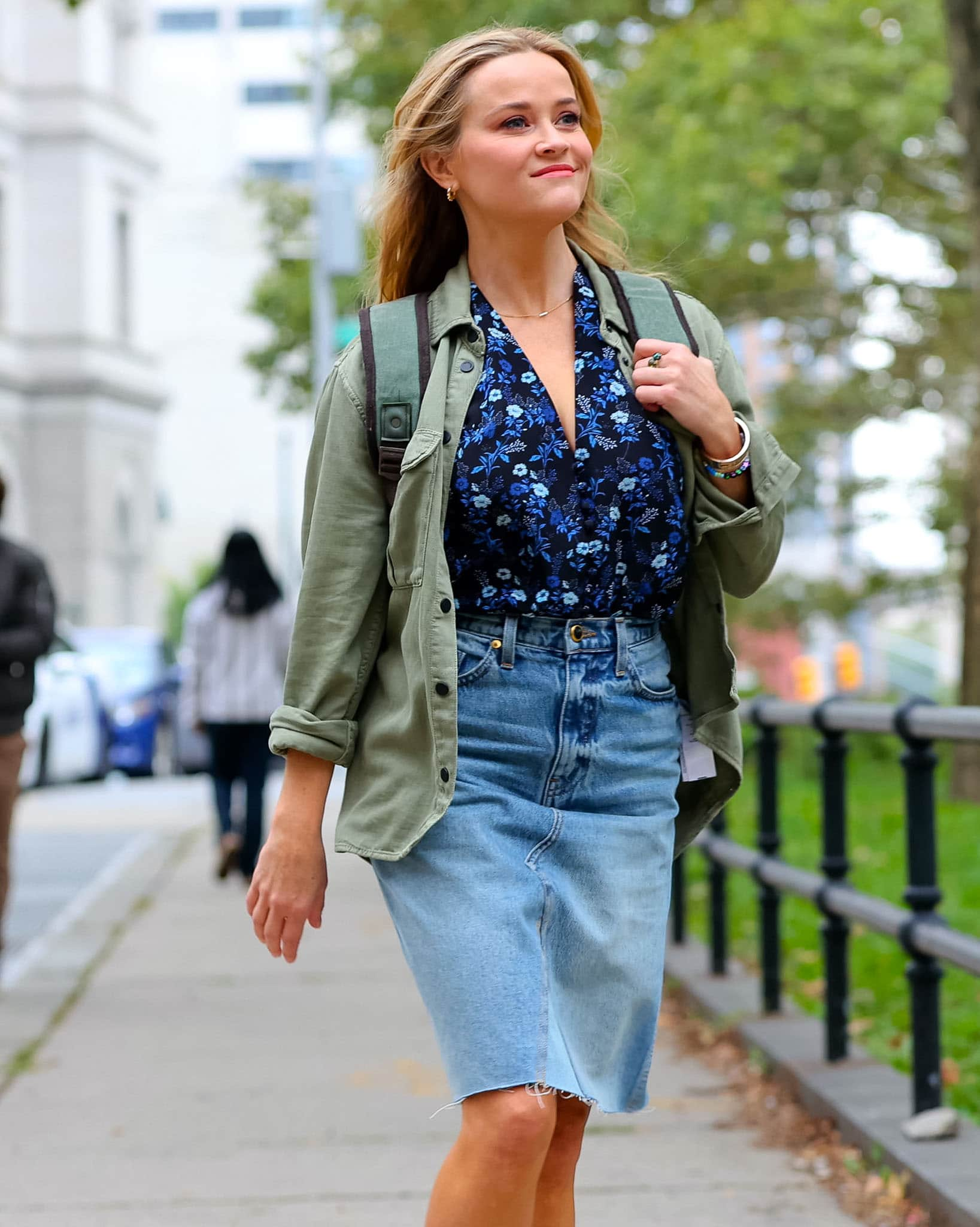 Reese Witherspoon opts for a casual cool look with natural soft makeup, floral shirt, and denim mini skirt