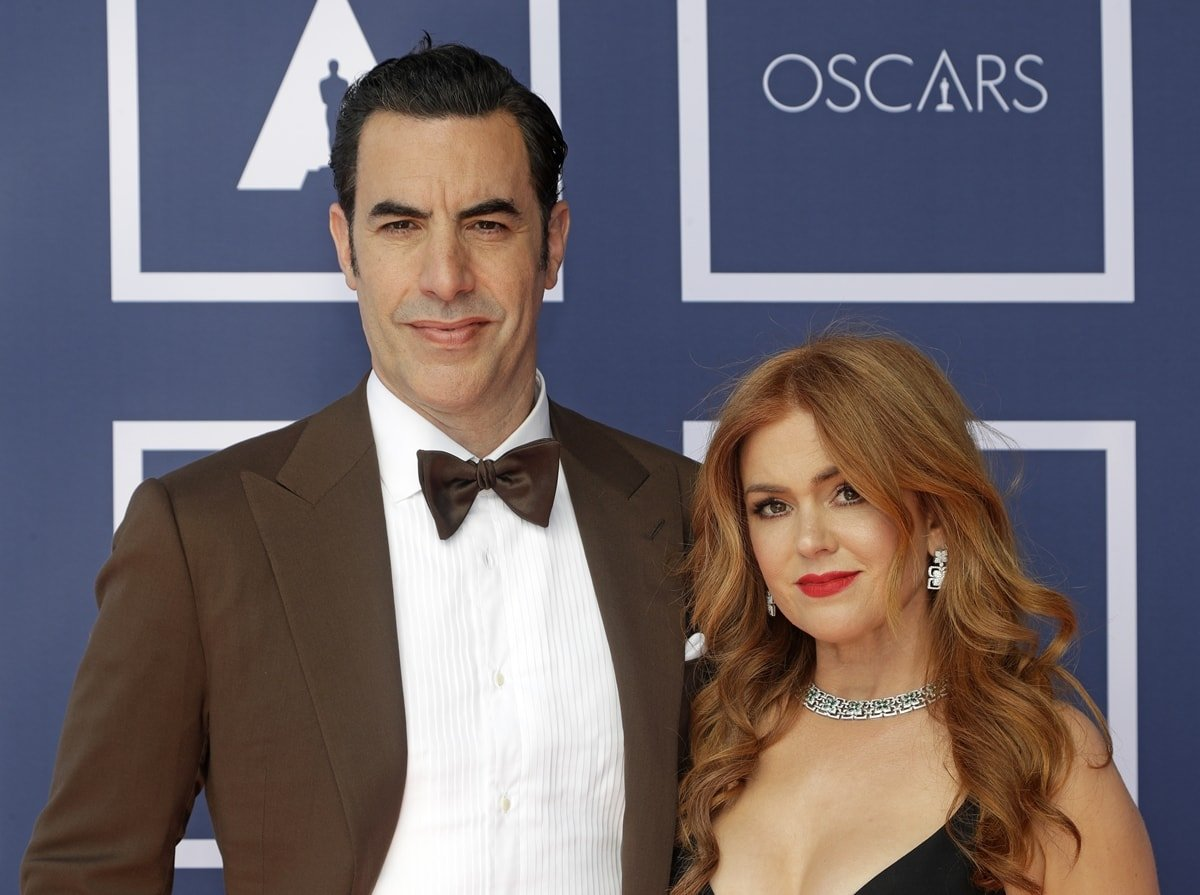 Isla Fisher wearing a Dior dress and Bvlgari jewelry with her husband Sacha Baron Cohen in a Ralph Lauren Purple Label suit at a screening of the Oscars